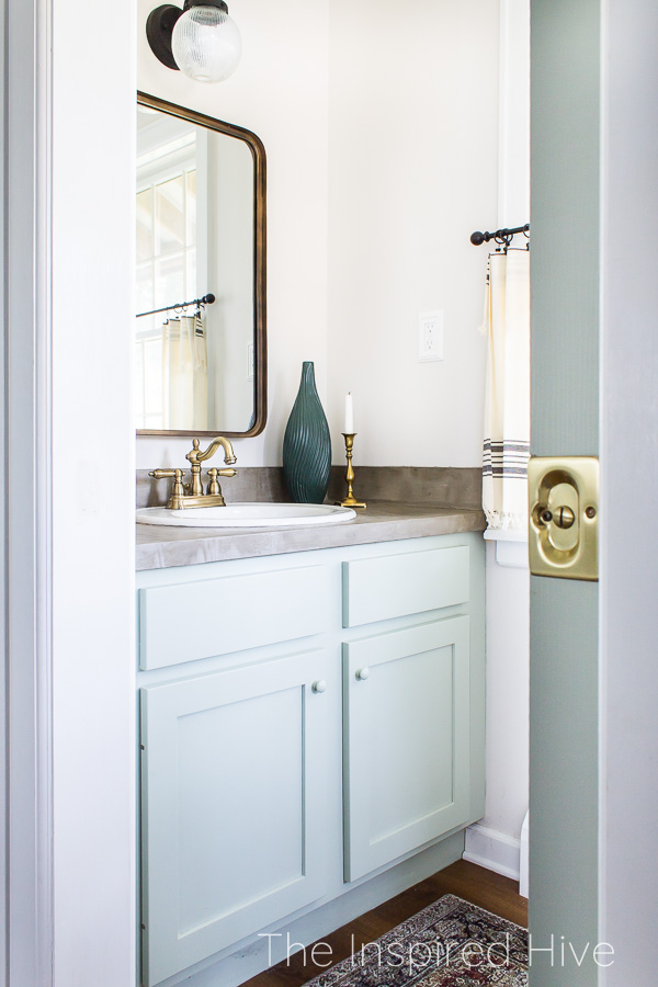 Ocean colored vanity, concrete countertop, brass faucet, and brass mirror in small powder room bathroom