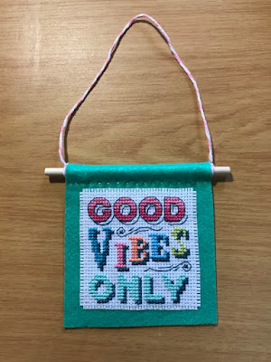 Good vibes only cross-stitch project mounted on green felt, stitched by Linzé Brandon