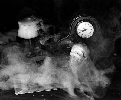 An open book, a skull, clock and beaker of foggy liquid.