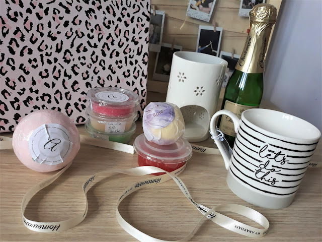 The image shows a pink leopard print gift box with lots of pamper treats inside. There is 2 bath bombs, wax melts, a mug, champagne, galaxy chocolate, cadbury's fingers and a wax burner in the box. It's sitting on a light brown wooden table.