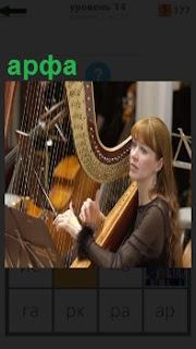 Девушка музыкант сидя играет на инструменте арфа, перебирая руками струны
