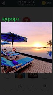 На берегу моря на курорте лежаки и зонт сверху, пальма вдали