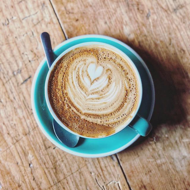 Latte Filled Blue Ceramic Cup on Saucer | Photo by Jason Thomas via Unsplash