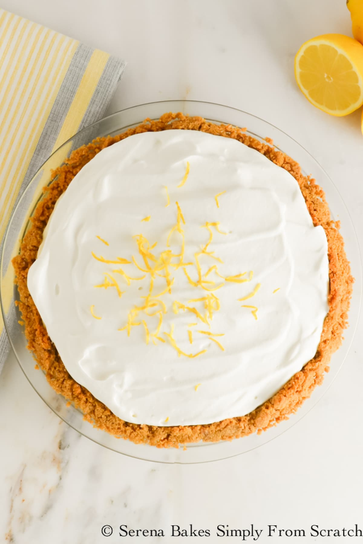 Lemon Pudding Cheesecake in a graham cracker pie crust topped with whipped cream and grated lemon zest.
