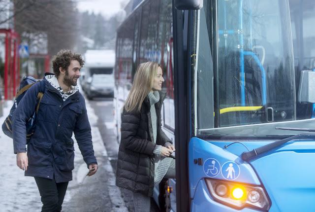 Mies ja nainen nousemassa bussin kyytiin.