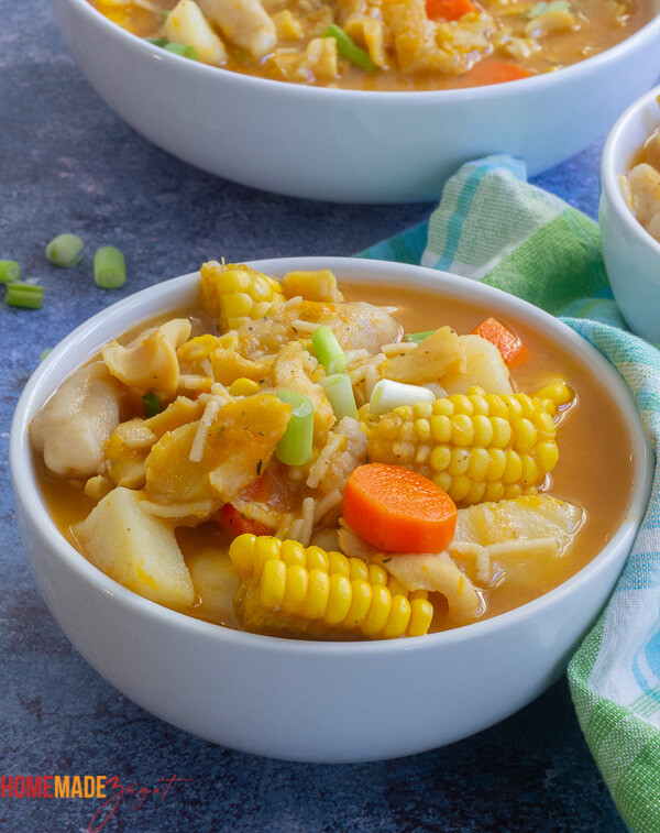 Close up of a full white bowl of conch soup with corn, potatoes, carrots and dumplings
