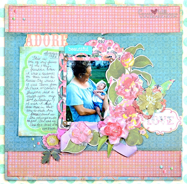 A pink, blue, and green scrapbooking page layout with K&Company die cuts and Prima Marketing velvety symphony flowers and enamel dots