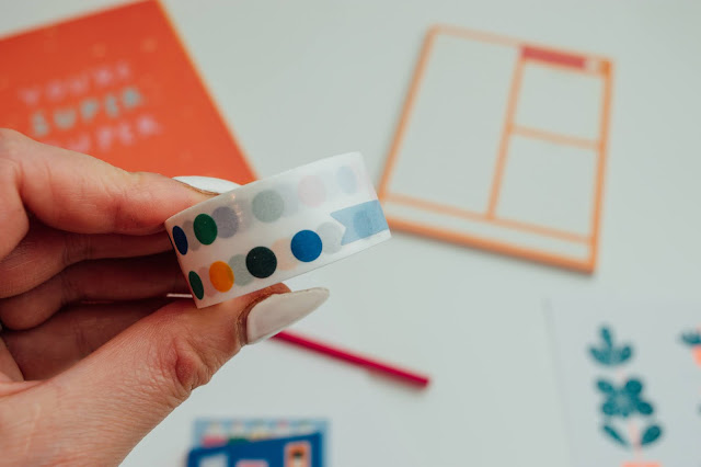 A hand holding up a roll of stickers with coloured dots
