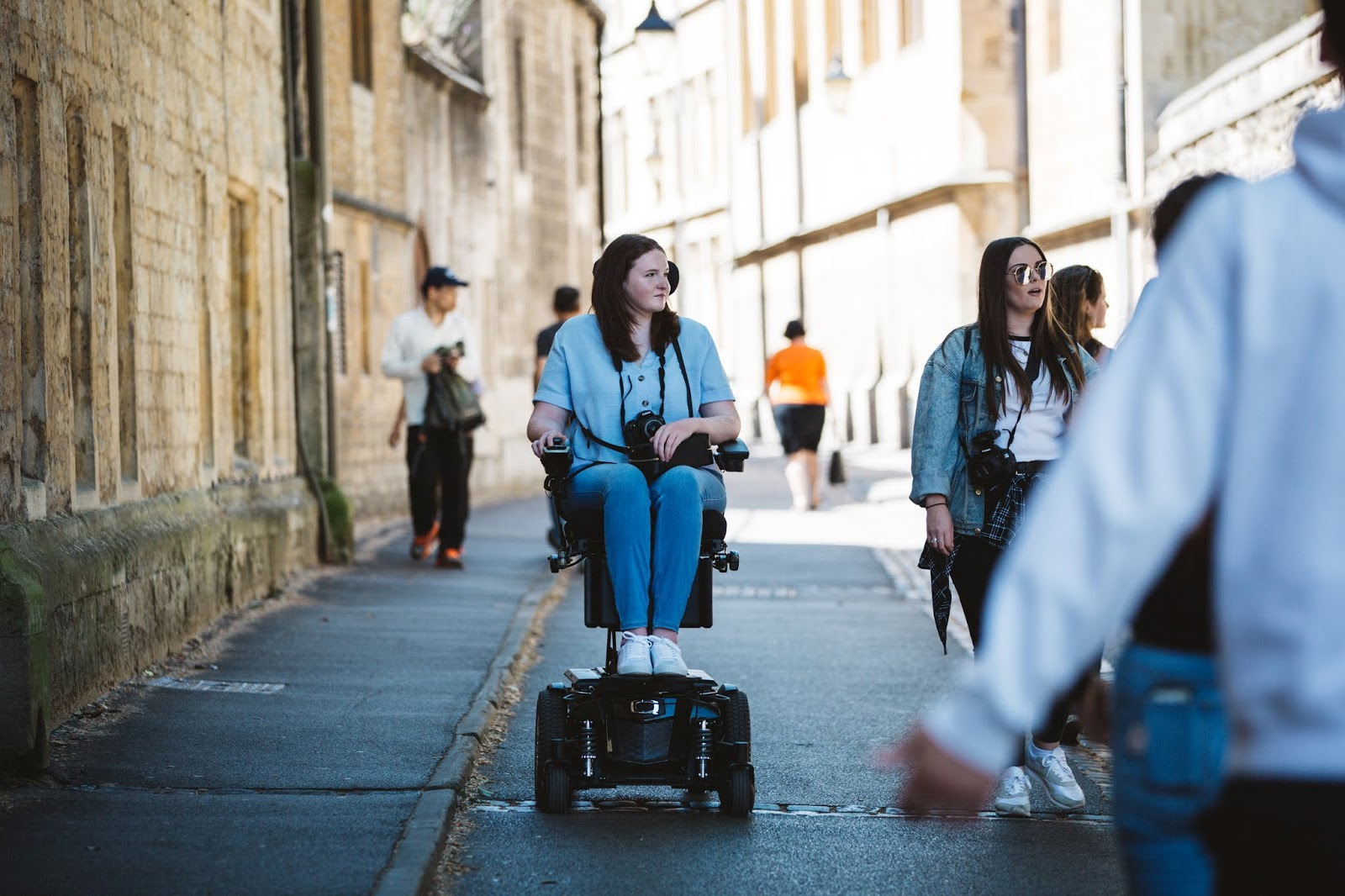 Shona, a powerchair user, is elevated in her powerchair and wheeling down a street amongst other people.