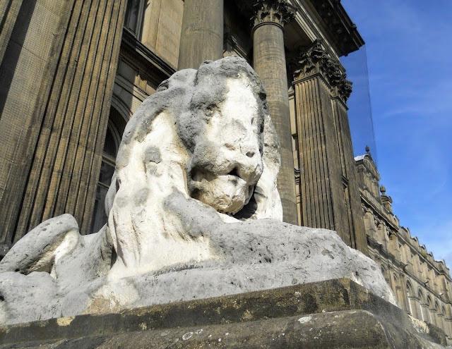 Weather-worn stone lion in Leeds England
