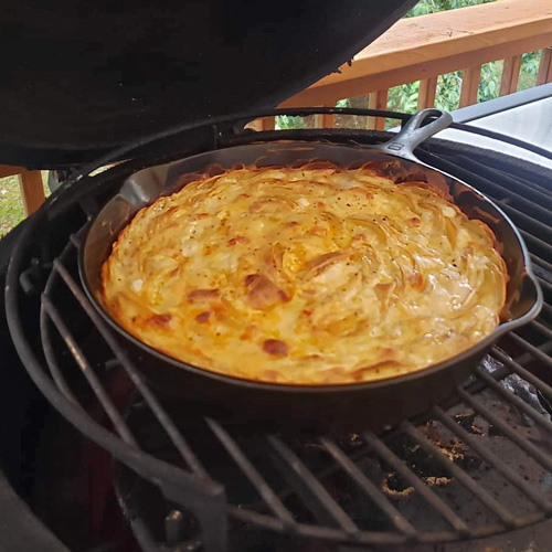 Skillet potatoes au gratin cooked on the Big Green Egg kamado grill.
