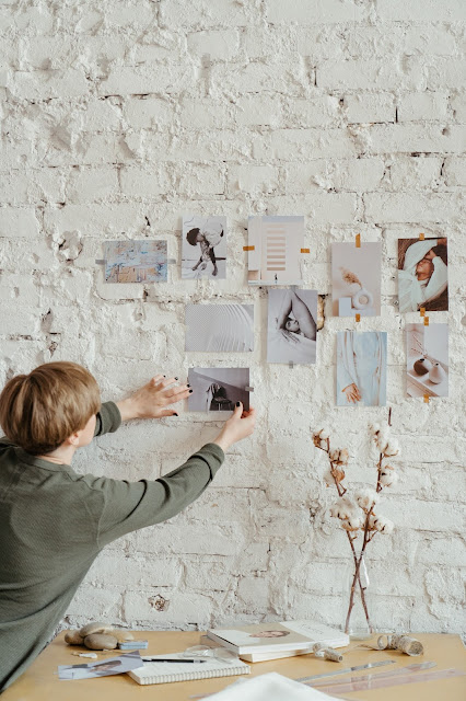 A person putting up pictures on a white wall for their vision board.