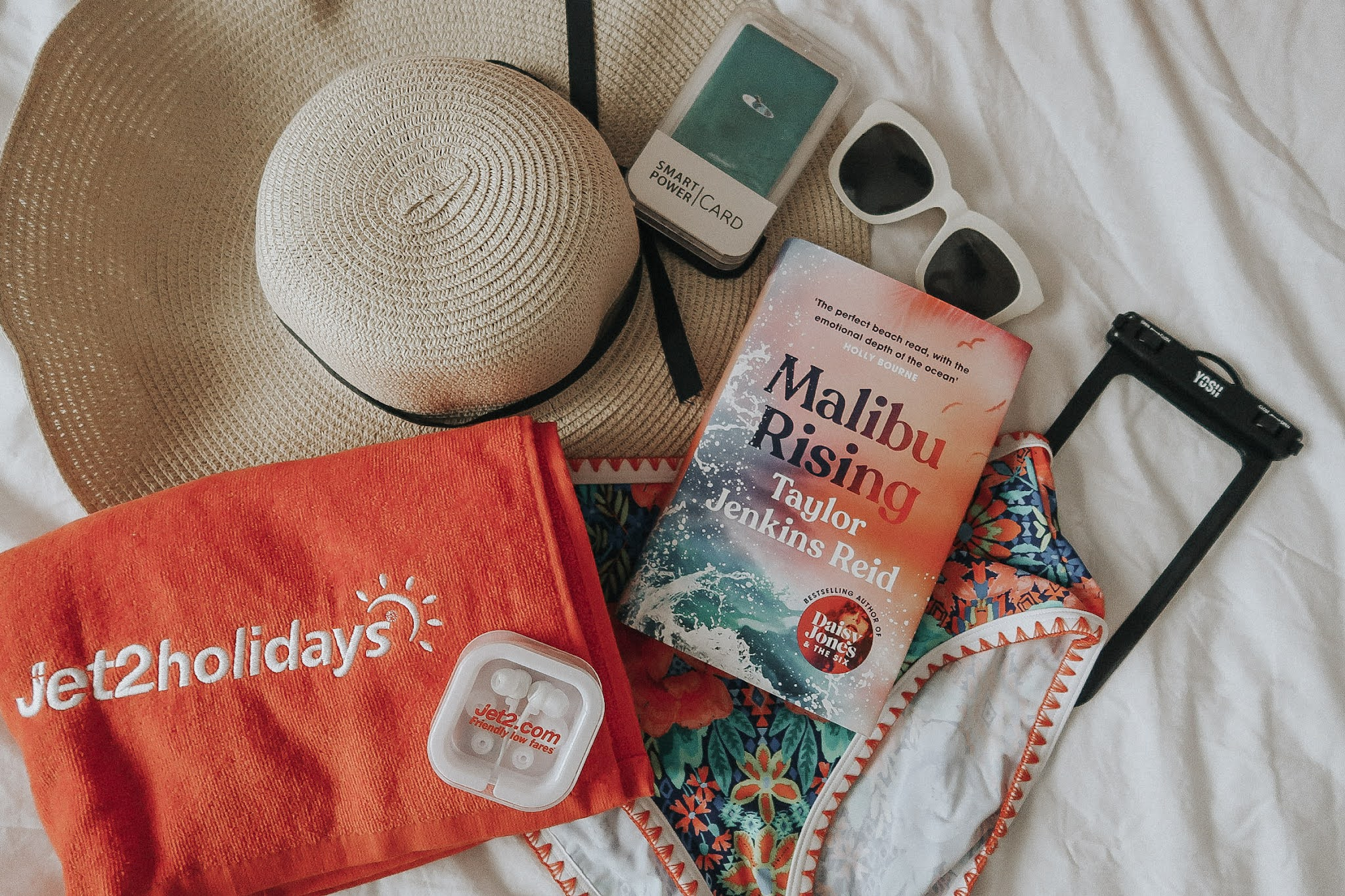A red beach towel, a pink book, white sunglasses and large beach hat.