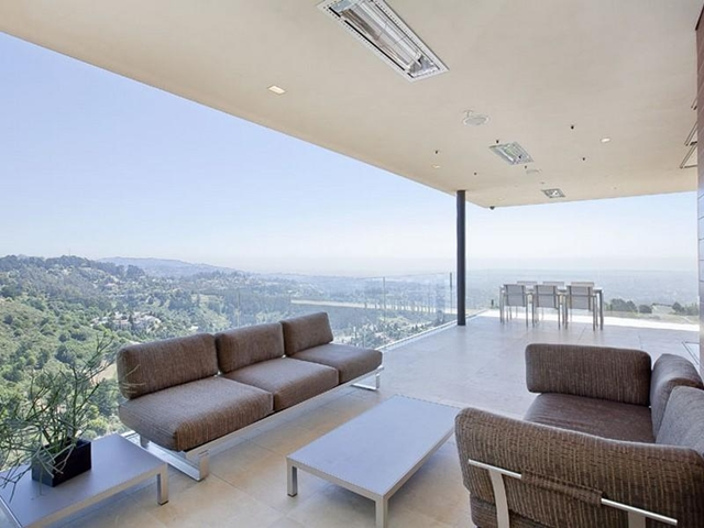 Photo of living room with glass wall and incredible views of surrounding hills