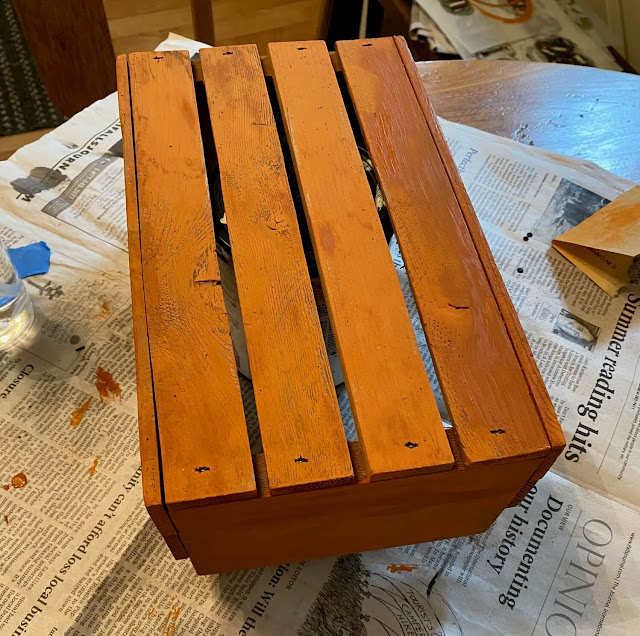 Photo of a slatted crate painted orange