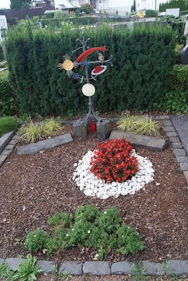 Eine Grabstätte mit einem Herz aus weißen Steinen, darin rot gepflanze Blumen. Hinten steht ein eisernes Kreuz mit verschiedenfarbigen Planeten