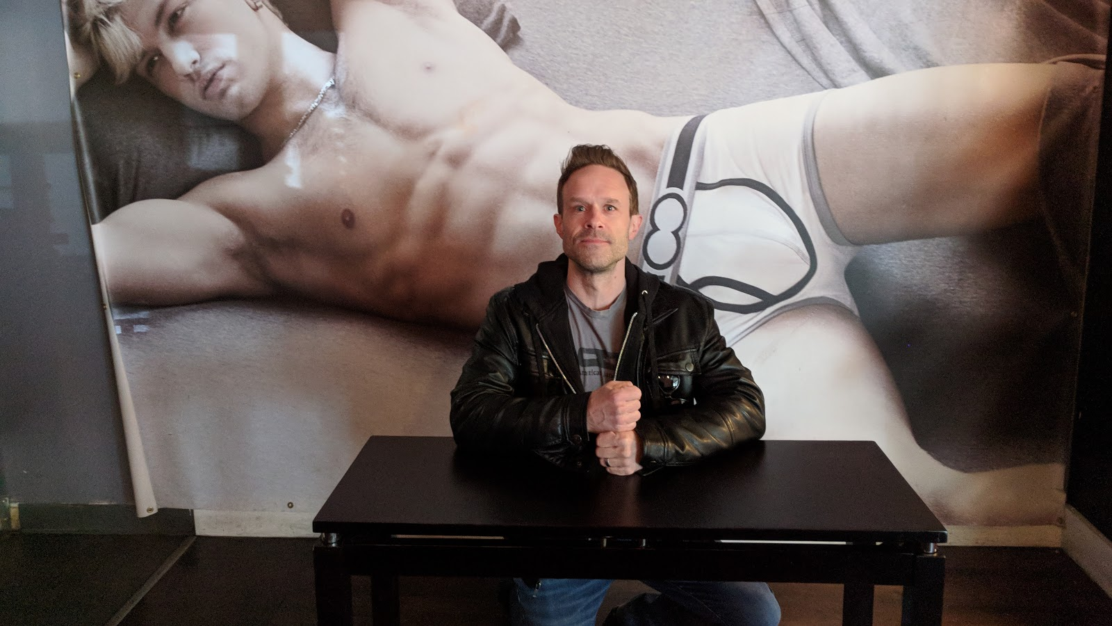 Image of Tom Ray at table in front of giant model in his underwear