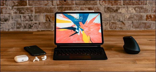 iPad Pro مزودًا بلوحة مفاتيح Magic والماوس و iPhone 11 Pro و AirPods على مكتب.