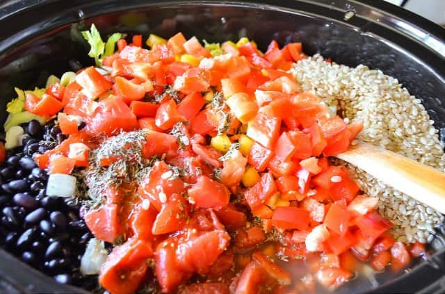 Crock Pot with Black Beans, Brown Rice, Garlic, Tomatoes, Bell Pepper, Herbs for Black Beans and Rice with Sausage.