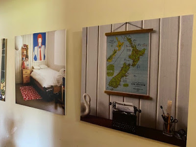 3 large blown up photos of 1/12 scale modern miniature scenes on display on a wall.