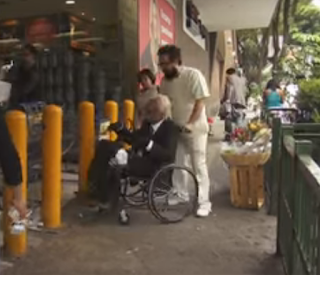 Entrando al súper en silla de ruedas.