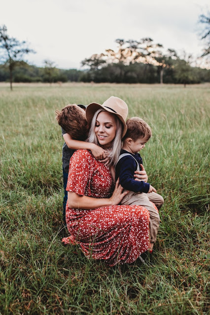 Mother in a field holding her two sons