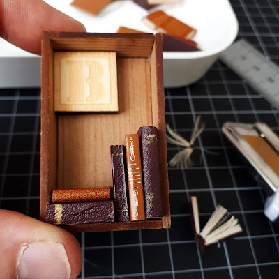 Hand holding a miniature wooden box frame containing a wooden 'B' tile, and five light and dark brown books stacked inside. In the background is a cutting mat, retractable knife, rulerm container of miniature books and some pieces of cut books.