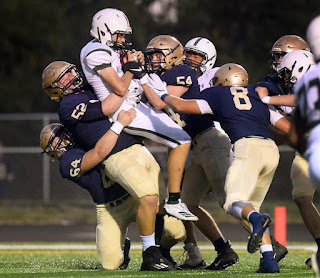 a group of Bishop Heelan football players from Sioux City work together to tackle a player from another team