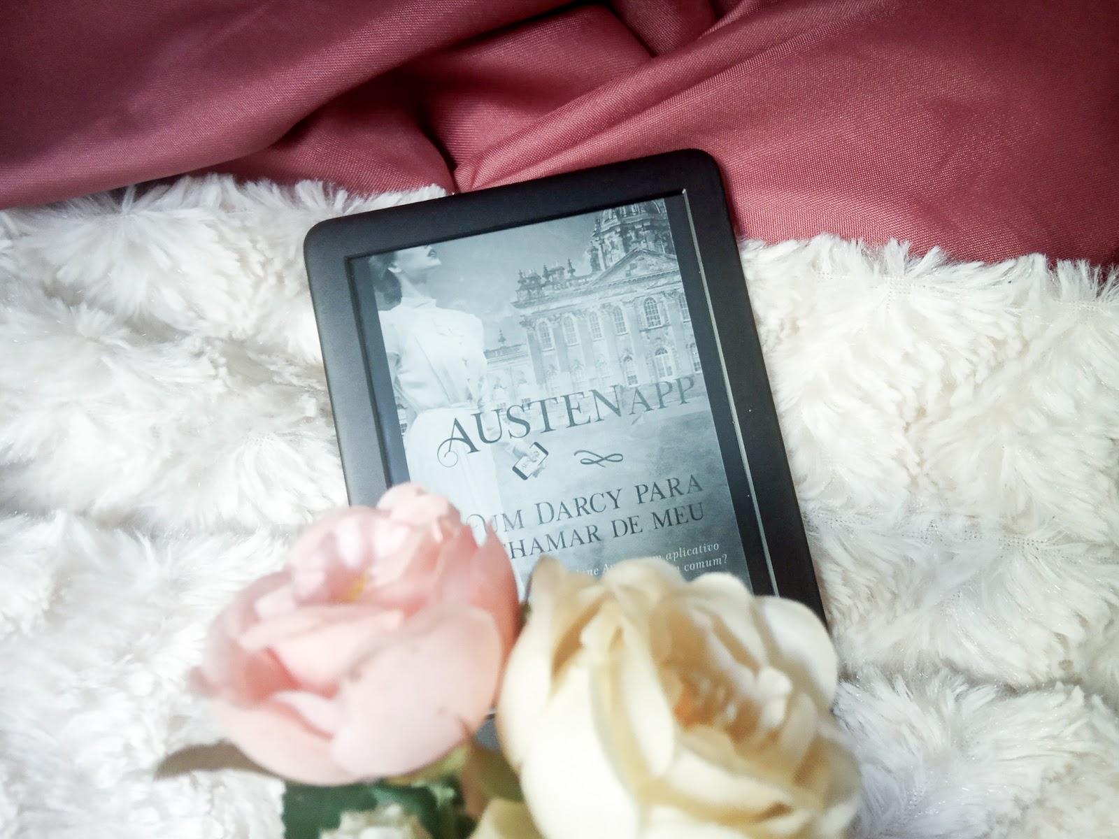 Foto com fundo mesclado de tecido liso cor de vinho e branco peludo com um aparalho kindle em cima contendo a capa do livro AustenApp e flores em baixo.