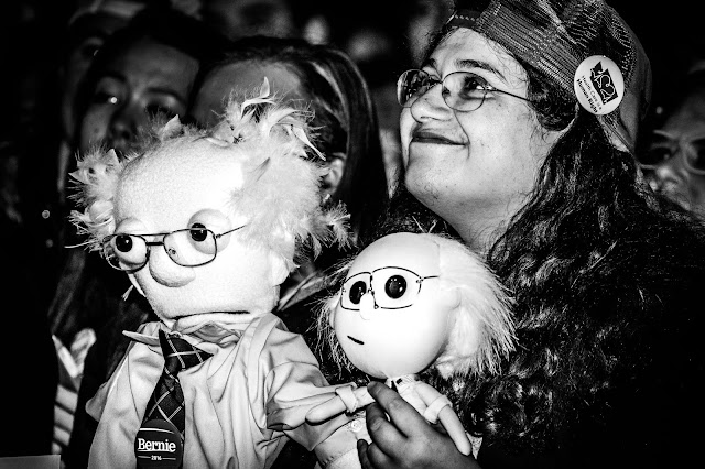 Black and white photo of a white woman wearing glasses, looking upward and smiling, holding two Muppet-like dolls