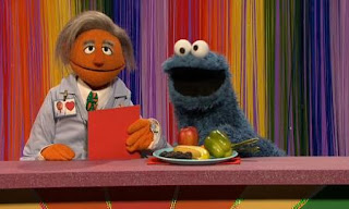 Dr. Ruster and Cookie Monster present the shows Eat Your Colors. Cookie Monster has fruits and vegetables on the plate in front of him. Sesame Street C is for Cooking