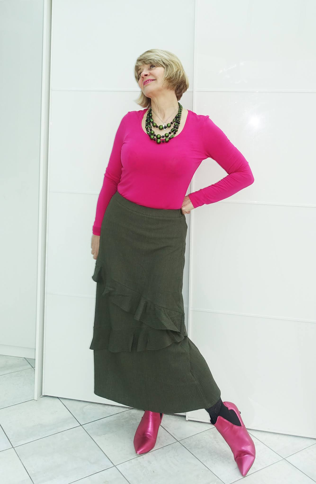 Gail Hanlon from over 50s style blog in khaki green tiered midi skirt and bright pink