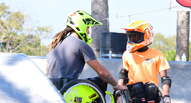 A main in a grey shirt, riding in a bright green manual wheelchair and wearing a matching motorcycle helmet, is shown talking to a young man who is also a manual wheelchair user. He rests his hand on the wheel of the other person's wheelchair. The young man is wearing a bright orange shirt. His wheelchair and motorcycle helmet match his shirt.