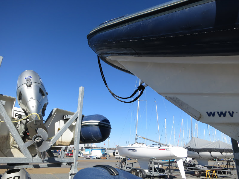 Boats in yard with big, silver motor and propellers