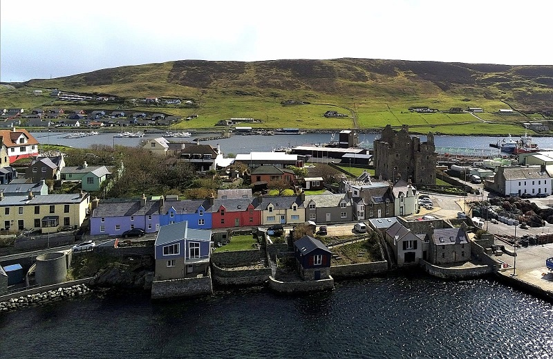 Row of colourful houses in front of Scalloway castle