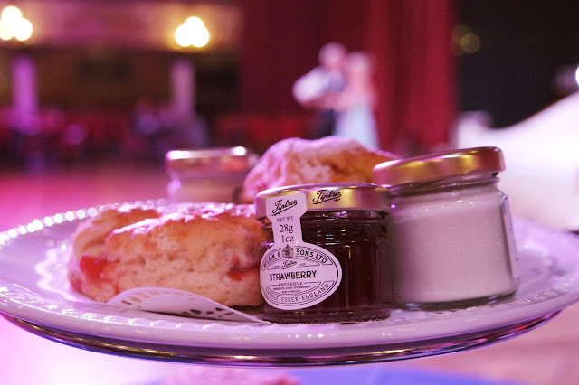 scones and small jars of jam on a plate, with dancers out of focus in the background