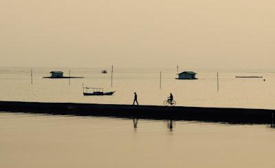 foto orang berjalan dan naik sepeda di pantai Pulau Harapan.