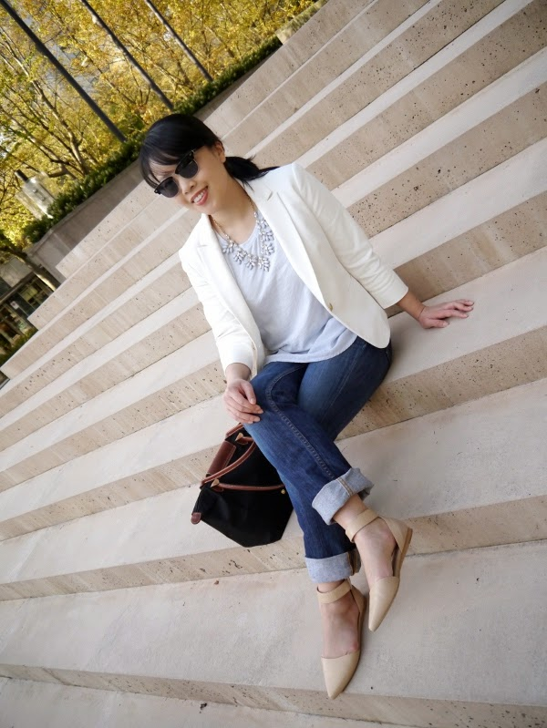 White blazer, powder blue silk and cotton tee, grey statement necklace, faded cuffed jeans, nude pointy-toe ankle strap flats