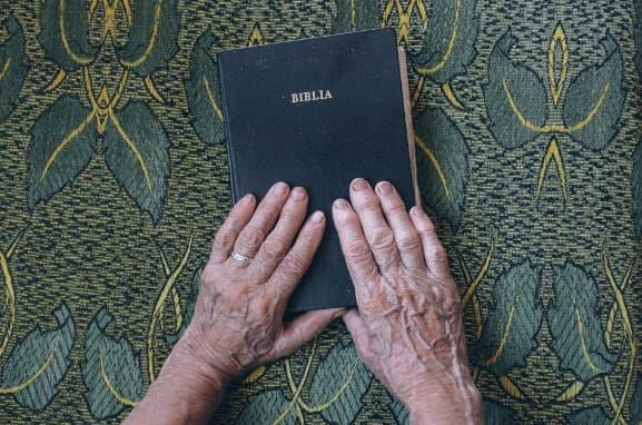 A imagem mostra mãos de uma pessoa idosa sobre uma bíblia
