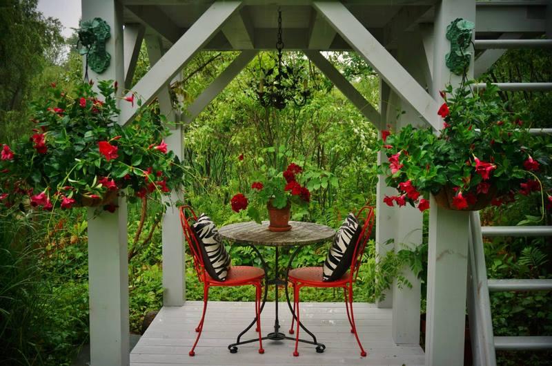 porche con columnas blancas, mesas, sillas y plantas en rojo