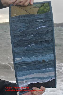 Hands holding denim seascape quilt