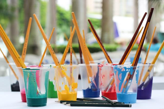 paintbrushes in plastic cups via unsplash.com