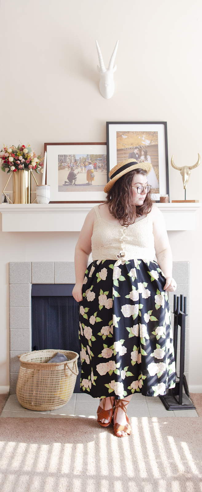 An outfit consisting of a wide brim straw boater hat, an off-white tie up lace crop top, black floral skirt, and brown tie up sandals.
