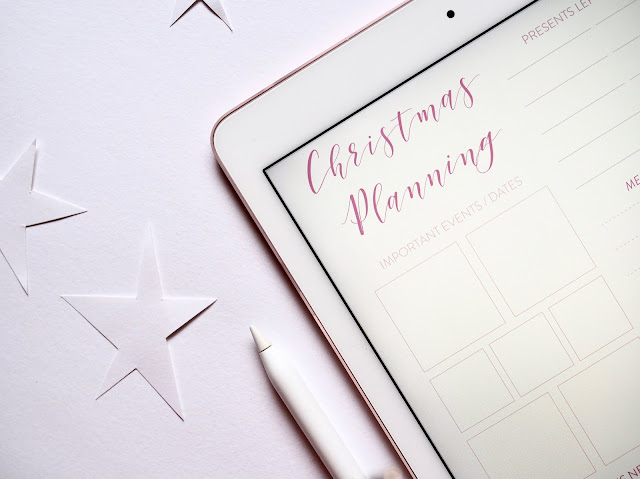 Flatlay showing a tablet that shows Christmas planner template, surrounded by stars and a pen