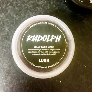 A circular clear plastic tub containing a brown circular face mask with a red ball in the middle of it with a black label saying Rudolph in big white font with face mask in smaller white font on a white background