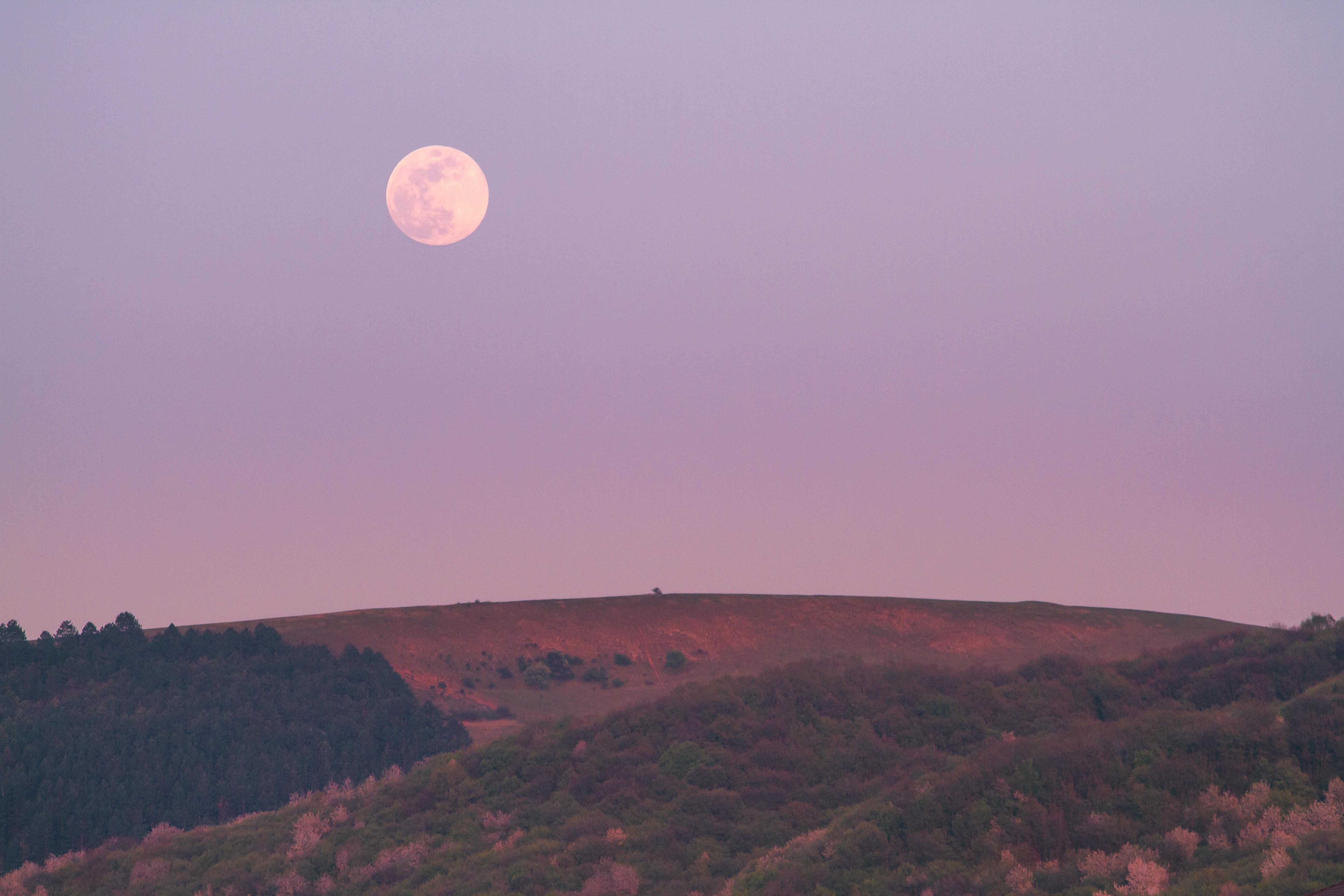 Heuvellandschap met de maan die aan de hemel staat.