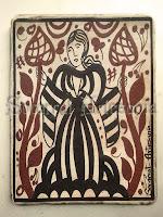 Esta dama de mangas anchas y falda larga, sujeta en cada mano un árbol de la vida, símbolo éste muy común en épocas pretéritas. Soc-art