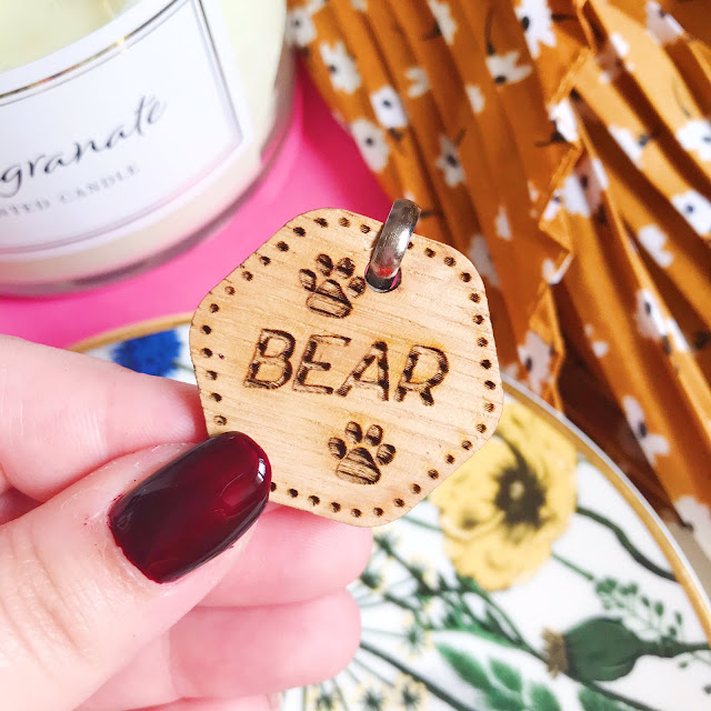 Holding personalised wooden tag above flatlay