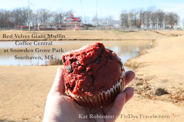 A red velvet muffin held up by a hand in front of a view of a pond and athletic complex at Snowden Grove Park in Southaven, MS