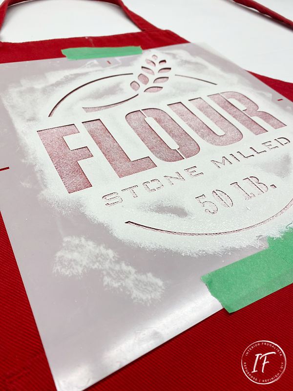 A festive red apron stenciled with flour sack stencils with farmhouse style for the kitchen plus a tutorial on how easy it is to stencil on fabric.
